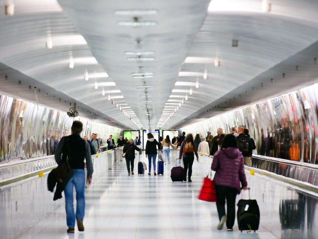 Mehrere Passagiere gehen mit ihren Koffern Richtung Ausgang