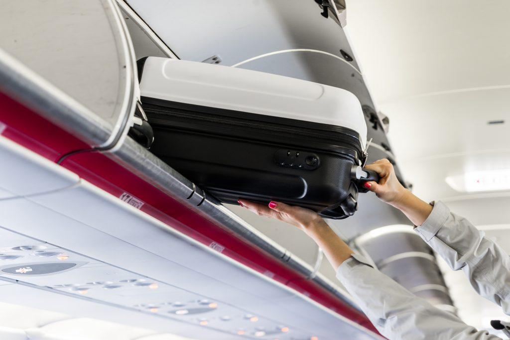 Eine Frau verstaut im Flugzeug ihr Handgepäck
